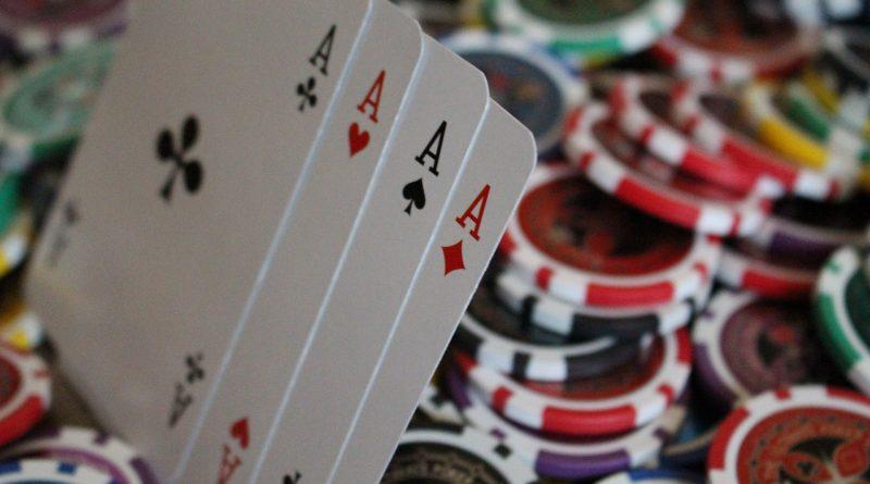 Zacięta partia pokera, na stole leżą olbrzymie pieniądze